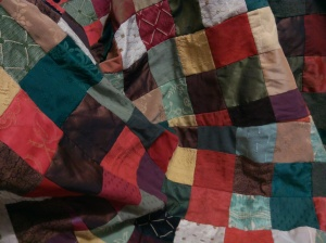 multicoloured patchwork cloak lining in greens, browns, yellows, rusts...